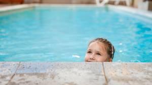 Ein kleines Mädchen schwimmt in einem Schwimmbecken.