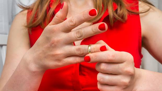 Eine Frau entfernt einen Ring von ihrem Finger
