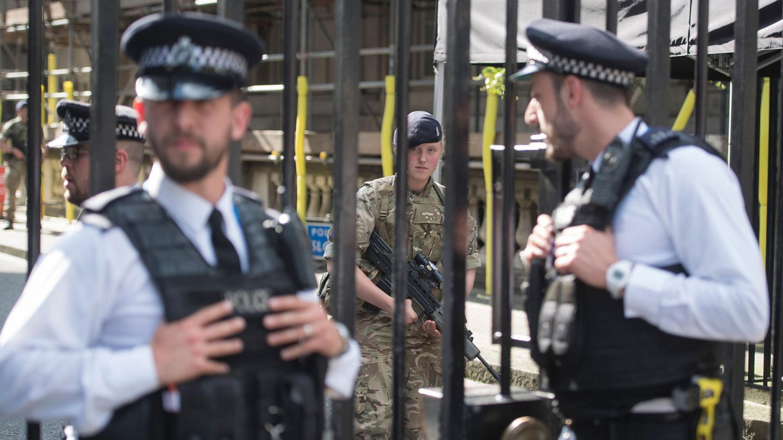 Soldaten und Polizisten bewachen die Downing Street in Westminster, London.