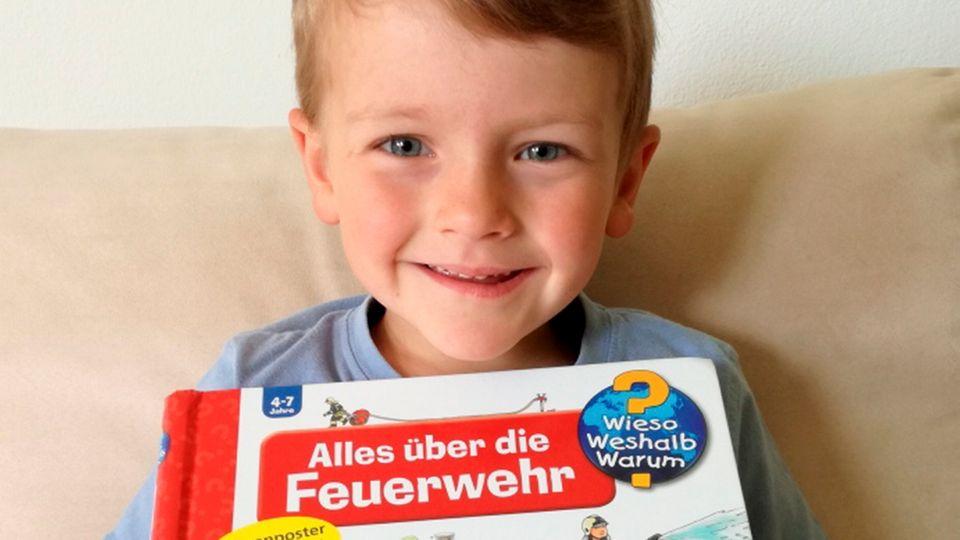 Der kleine Tobias zeigt strahlend sein Buch