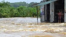 Unwetter in Sri Lanka: Ein Bewohner steht im Eingang seiner Hütte und blickt auf die Fluten