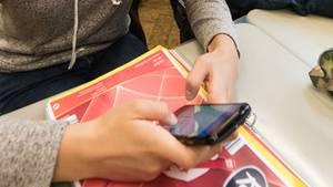 Ein Kind tippt auf einem Handy