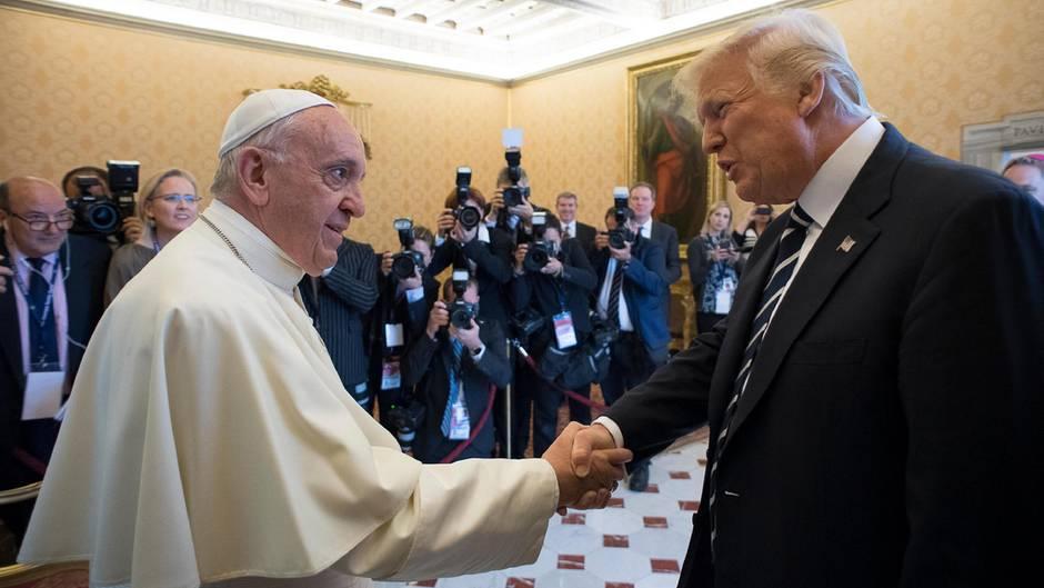 US-Präsident Donald Trump und Papst Franziskus schütteln sich im Vatikan die Hand. Im Hintergrund arbeiten Fotografen.