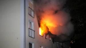 Flammen schlagen aus dem Fenster einer Wohnung in einem Mehrfamilienhaus in Flensburg.