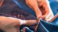 Zwei Frauenhände stecken an einer Jeans eine Naht ab