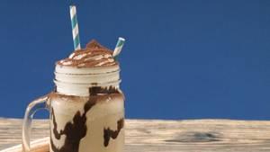 Aus einem Trinkglas mit Sahnehaube ragen zwei blau-weiß geringelte Strohhalme heraus. Im Glas eine kakaofarbene Flüssigkeit.