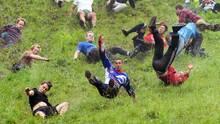 """Gloucestershire, Großbritannien. Die Teilnehmer des ersten """"Käserennens"""" in Aktion. Bei der skurrilen Veranstaltung laufen die Teilnehmer einem Käselaib hinterher, der einen Hügel herunterrollt. Die Tradition geht angeblich auf die Römerzeit zurück. Als gesichert gilt, dass sie seit 200 Jahren durchgeführt wird. Das """"Cooper·s Hill Cheese-Rolling and Wake"""" ist eine viertägige Veranstaltung."""