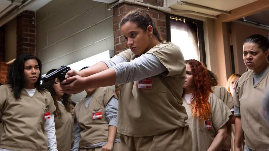 Ein Ausschnitt aus Orange is the New Black Staffel 5 zeigt Gefangene Darya mit Pistole