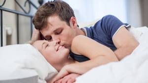 Ein Paar liegt zusammen im Bett (Symbolbild)