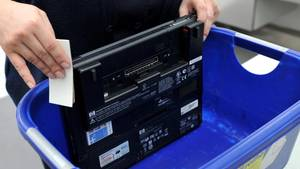 Ein Laptop in einem Plastikbehälter an der Sicherheitskontrolle am Flughafen