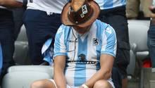 Ein Fan des TSV 1860 München im weiß-blauen Trikot sitzt mit hängendem Kopf auf der Tribüne