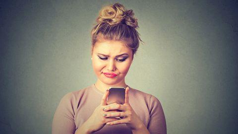 Eine Frau schaut genervt auf ihr Smartphone