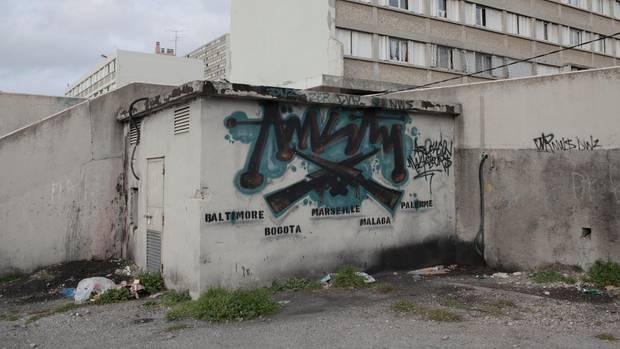 """Von Baltimore bis Palermo: Ein Graffito an der Zufahrt zur Cité """"Parc Kallisté"""" nennt Zentren des Drogenhandels."""