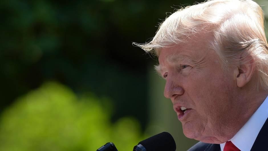 US-Präsident Donald Trump - im Profil fotografiert - spricht vor dem Weißen Haus in ein Mikrofon und gibt eine Erklärung ab