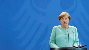Bundeskanzlerin Angela Merkel steht im mintgrünen Kostüm vor einer blauen Wand, auf der der Bundesadler zu sehen ist