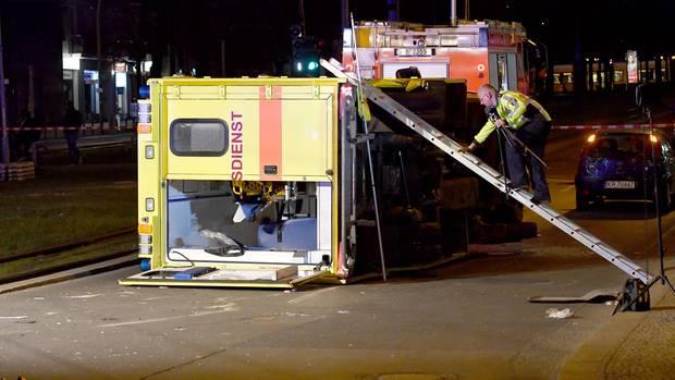 Ein Polizist klettert am 27. März.2017 in Berlin am Frankfurter Tor über eine Leiter auf einen umgestürzten Krankenwagen. SiebenPersonen wurden bei dem Unfall verletzt.