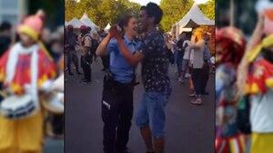 Eine Polizistin tanzt mit einem Besucher beim Karneval der Kulturen in Berlin zu Sambarythmen
