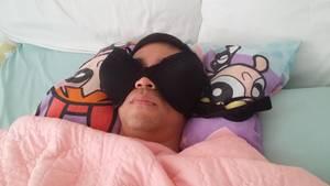 Mann liegt im Bett und nutzt Busenhalter, statt Schlafbrille