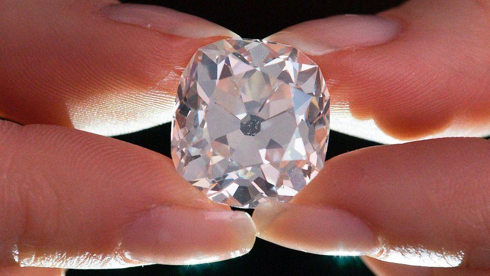 Ein Mitarbeiter des Auktionshauses Sotheby's hält zwischen Daumen und Zeigefingern einen Diamantring