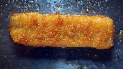 Ein Fischstäbchen liegt in einer fettigen Pfanne und wird gebraten