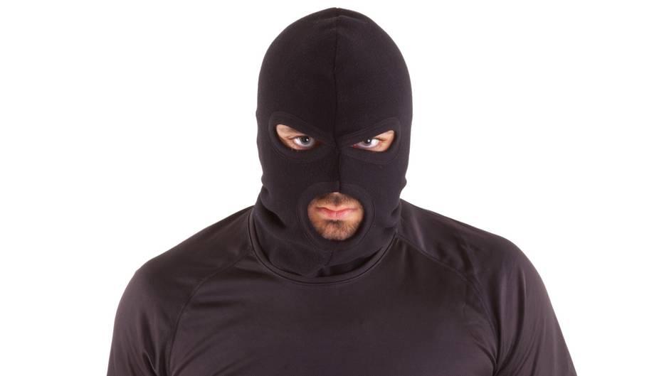 Ein Mann mit schwarzer Sturmhaube und schwarzem T-Shirt schaut grimmig