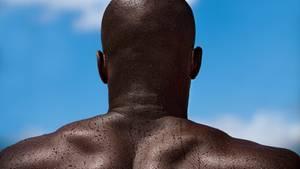 Ein schwarzer Mann mit nacktem Oberkörper und mit Glatze von hinten