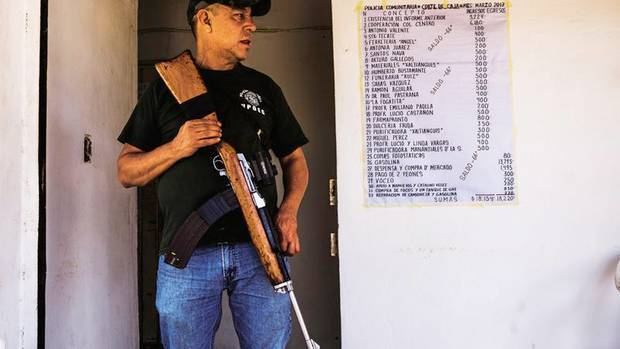 Comandante Carlos Pájaro vor seiner Wache. Neben ihm hängt das Budget der Truppe, für alle einsehbar