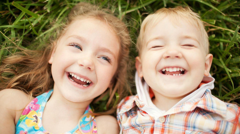 Geschwister liegen lachend auf einer Wiese