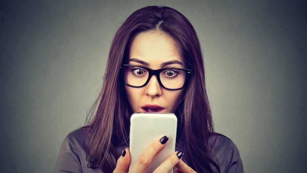 Ein Frau schaut entsetzt auf ihr Smartphone. Ob Facebook installiert ist, ist nicht zu sehen