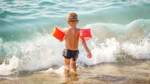 Ein Kind spielt mit Schwimmflügeln am Strand