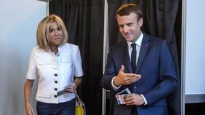 Emmanuel Macron und seine Frau Brigitte verlassen ihre jeweiligen Wahlkabinen bei der Wahl in Frankreich