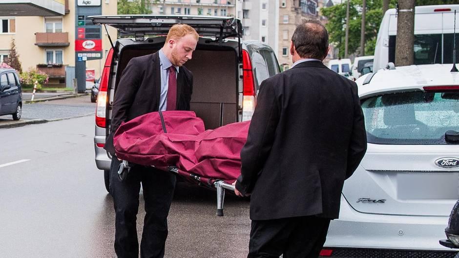 Bestatter tragen in Nürnberg die Leiche einer Frau aus einer Wohnung. Die Polizei hat die Prostituiertenmorde jetzt aufgeklärt.