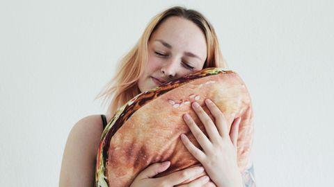 Die Autorin drückt ein Kissen in Form eines Döners liebevoll an ihr Gesicht.