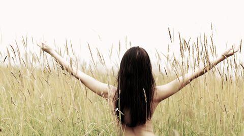 Eine von hinten fotografierte Frau steht mit nacktem Oberkörper in einem Feld