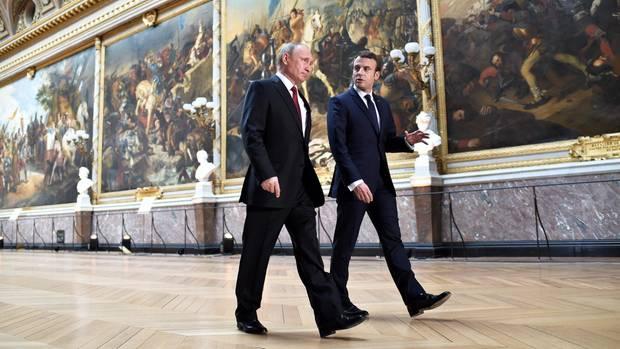 """Durch die """"Galerie der Schlachten"""" in Versailles geleitet Macron den russischen Präsidenten Putin zum Gespräch über Krisengebiete wie Syrien und die Ukraine."""