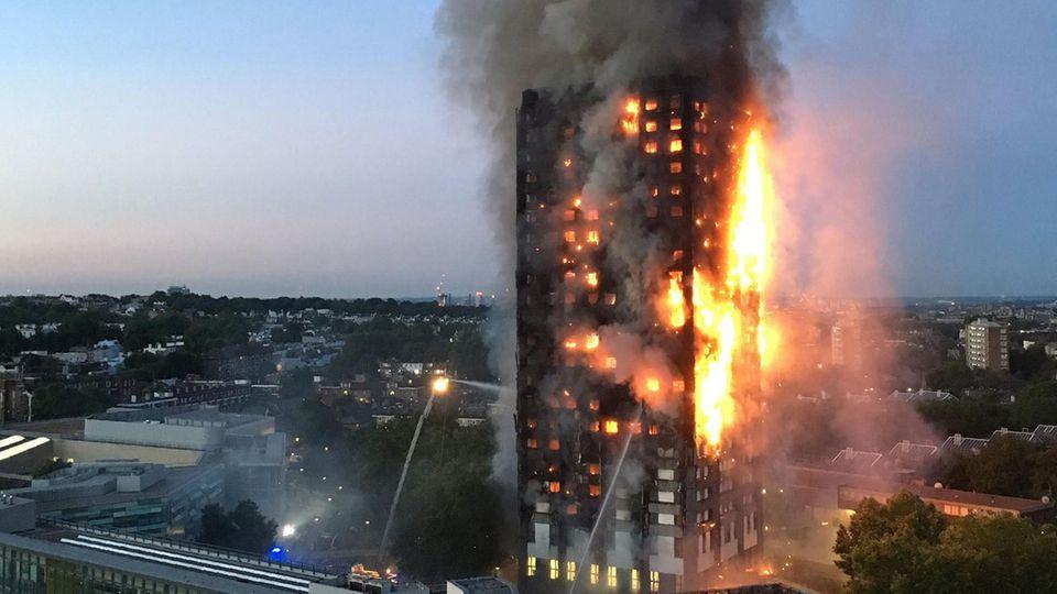 Ein Hochhaus in London brennt. Rechts schlagen Flammen über die gesamte Höhe aus der Fassade, links Feuerschein hinter Fenstern