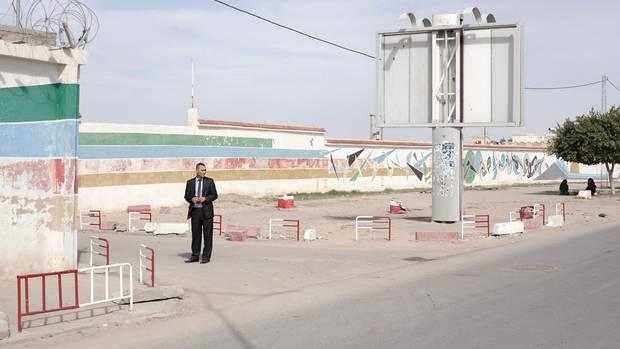 Ein Mitarbeiter des Gefängnisses Kasserines wartet vor dem Eingangstor auf Ali Rebah.
