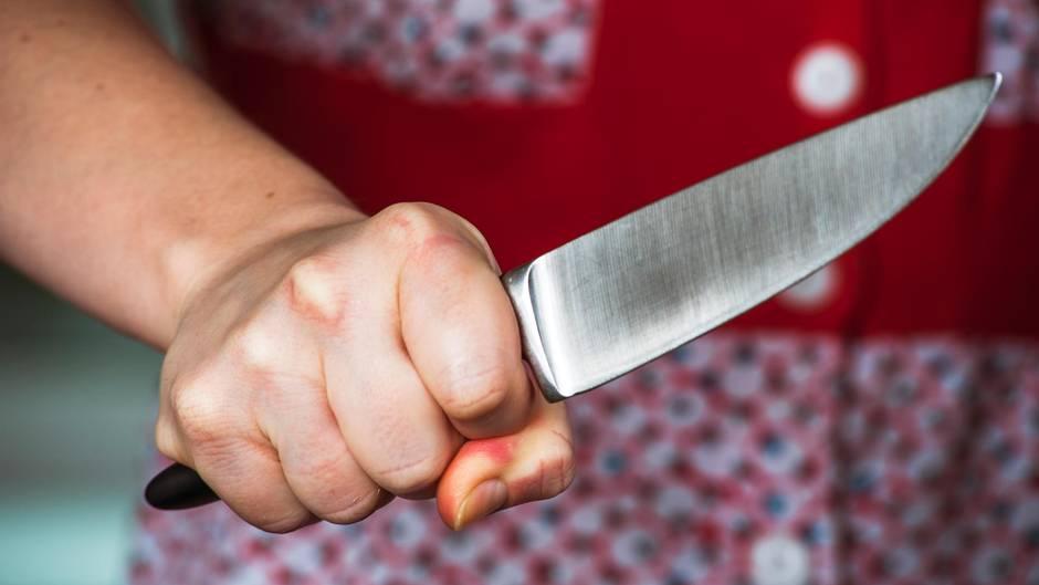 Eine Frau hält ein Messer in der Hand