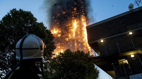 Ein Feuerwehrmann blickt auf den lichterloh brennenden Grenfell Tower in London