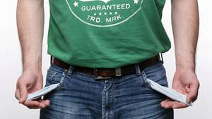 Singles leben oftmals deutlich teurer - ein Mann zeigt die leeren Taschen seiner Jeans-Hose