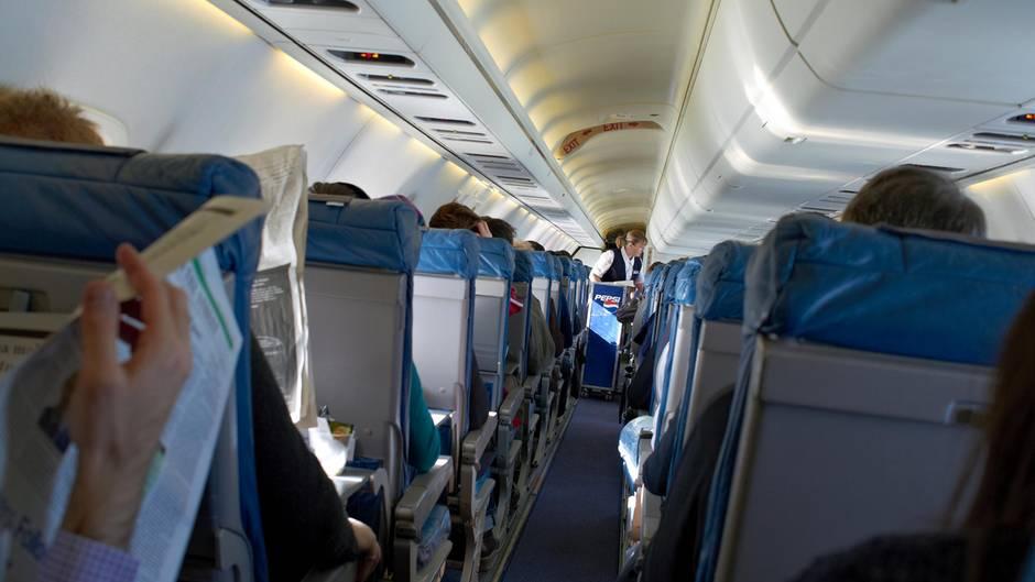 Fluggäste sitzen an Bord eines Flugzeuges, während eine Flugbegleiterin im Gang Getränke verteilt