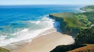Eine wunderschöne Bucht mit Sandstrand, blauem Meer und grüner Natur drum herum.