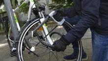 Ein Mann stiehlt ein Fahrrad (Symbolbild)