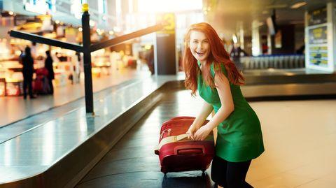 Sabbatical: Eine Frau holt ihren Koffer von einem Gepäckband am Flughafen