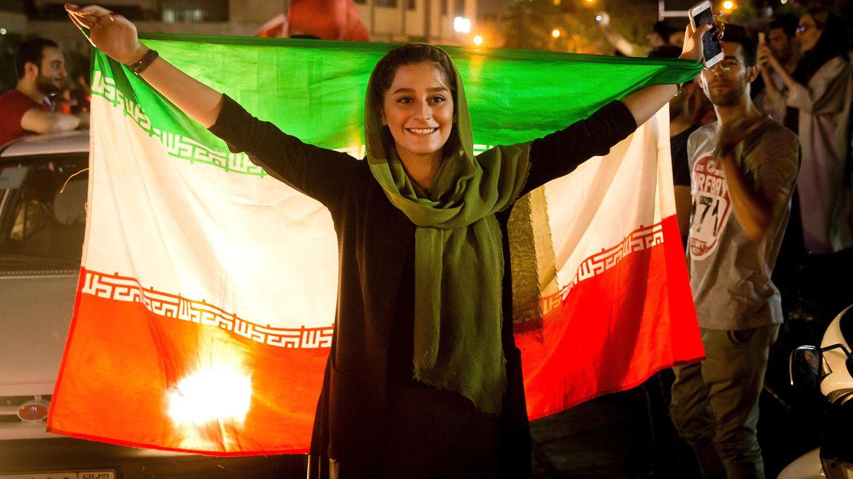 Ein iranische Frau feiert mit der Nationalflagge die Qualifikation des Herren-Fußballteams zur WM 2018 in Russland