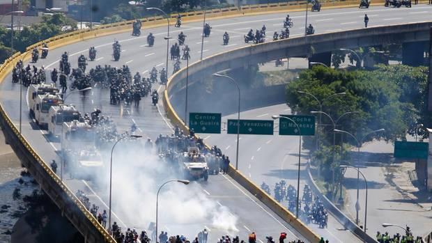 Auf einer Schnellstraße treffen hochgerüstete Polizeieinheiten und Demonstranten aufeinander
