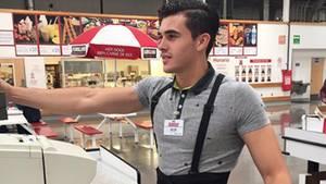 Ein hübscher junger Mann arbeitet an einer Supermarktkasse