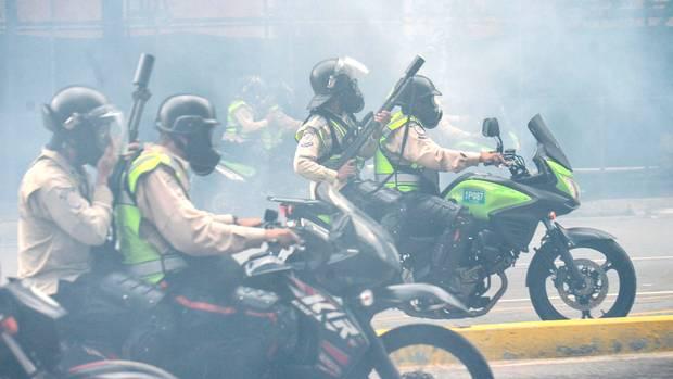 Polizeieinheiten auf Motorrädern gehen mit brutaler Gewalt gegen die Menschen vor. Die Luft ist geschwängert von Tränengas