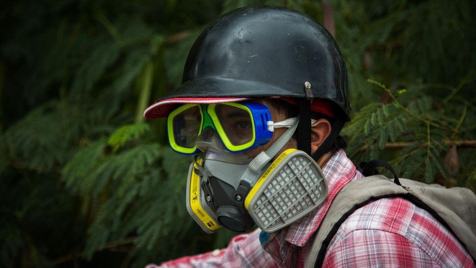 Jo Gomez mit Helm und Gasmaske. Der Sozialarbeiter sagt, der Hass sei nicht mehr zu kontrollieren