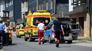 Ein Rettungswagen und ein Polizeiauto stehen vor einem mit Schiefer verkleideten Haus, in dem sich ein Familiendrama abspielte